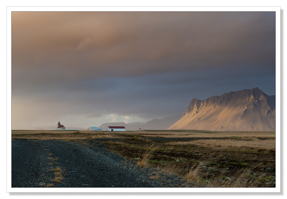 Landscape Photograph, Fáskrúðarbakkakirkja, church with sun dappling on the mountain, rain, waiting for the light, Iceland