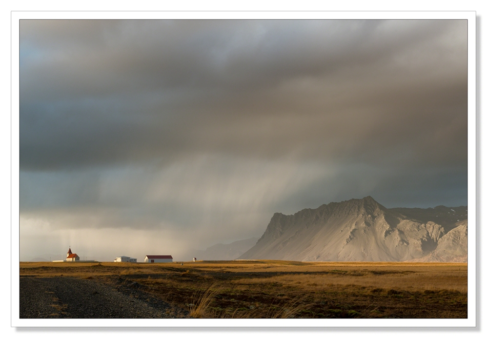 Landscape Photograph, Fáskrúðarbakkakirkja church with rain sweeping past towards the mountains, Iceland, waiting for the light