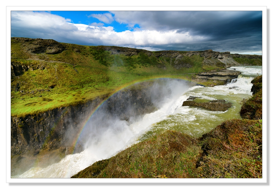 Gulfoss waterfall in summer showing a rainbow above the falls.